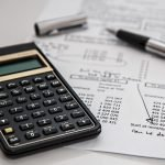 black-calculator-near-ballpoint-pen-on-white-printed-paper